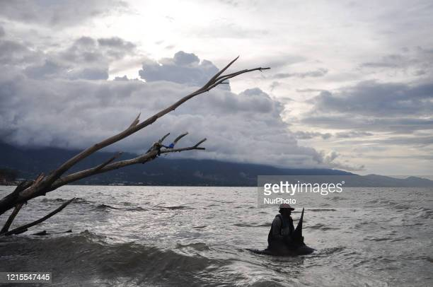 Fisherman tries to push a sunfish back into the sea after being stranded alive in Talise Beach, Besusu Village, Palu City, Central Sulawesi Province...