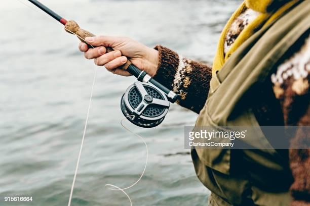 amarrando uma mosca em sua linha de pescador - pescador - fotografias e filmes do acervo
