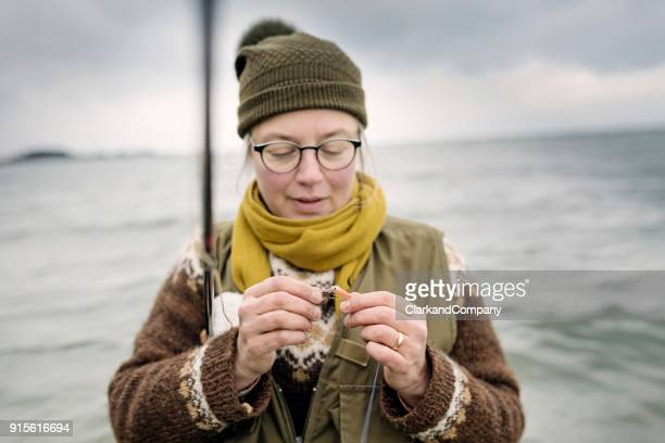 Fisherman Tying a Fly Onto Her Line