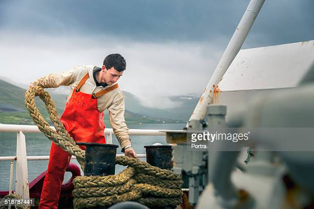 Fisherman tying rope on boat