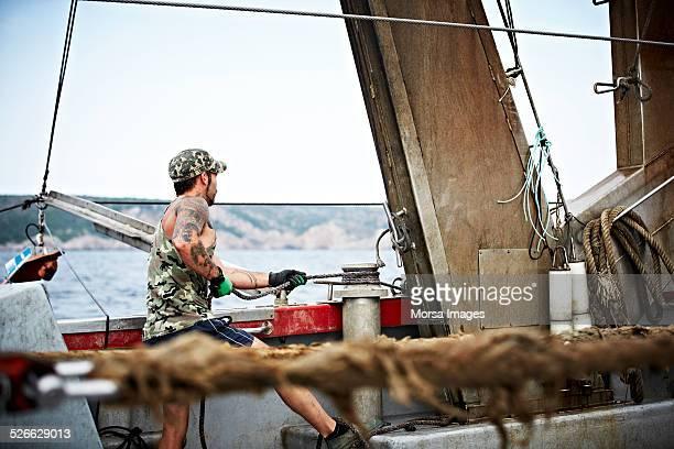Fisherman tying rope on trawler