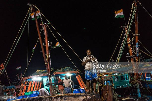 A fisherman uses a mobile phone on a fishing boat in the harbor in Puducherry India on Saturday July 19 2014 Indias gross domestic product growth...