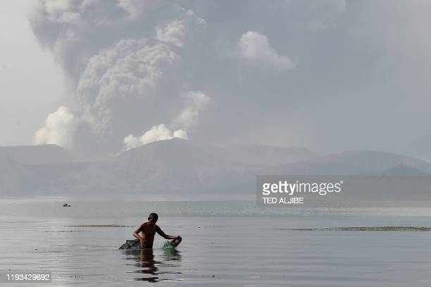 TOPSHOT A fisherman wades with his nets in the waters of Taal Lake as the Taal volcano spews ash as seen from Tanauan town in Batangas province south...