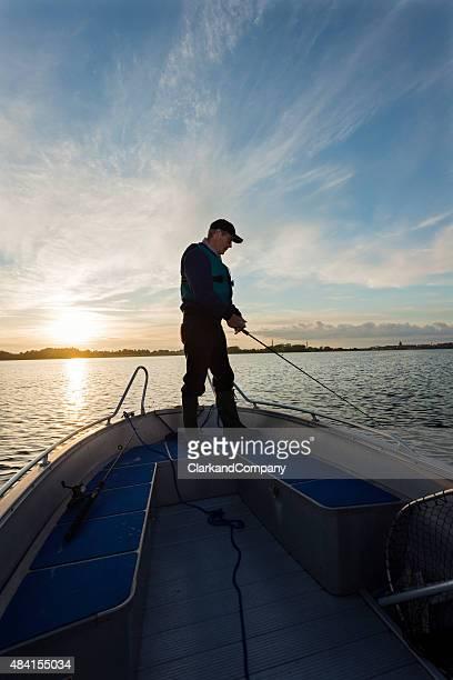 Pêcheur attend pour un en-cas sur sa ligne au coucher du soleil