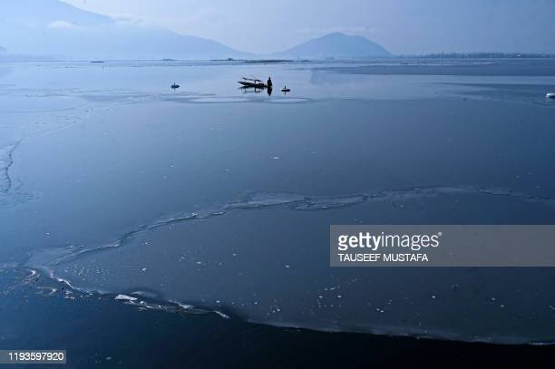 A fisherman waits after casting his net around a frozen part of the Dal Lake after heavy snowfall in Srinagar on January 14 2020