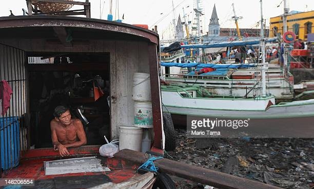 A fisherman waits in his boat docked at the historic VeroPeso market on June 7 2012 in Belem Brazil Belem is considered the entrance gate to the...