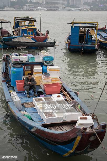 Fisherman waits on boat at shore of Gulangyu Island on November 12 2014 in Xiamen China Xiamen is located on the southeast coast of Mainland China is...