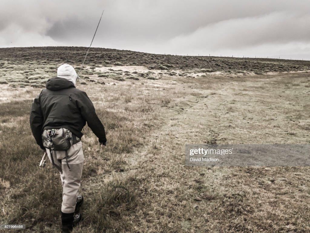 Fisherman walking to river : Stock Photo