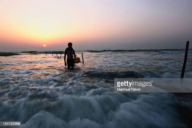 Fisherman walking towards sea shore