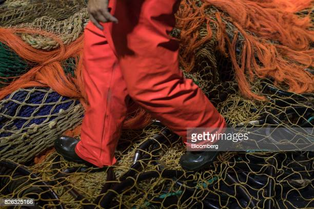 A fisherman walks on fishing nets on board a trawler before unloading the catch at the port of Den Helder Netherlands on Friday Aug 4 2017 Prime...