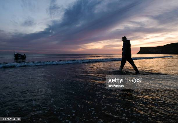 A fisherman walks out to his boat after launching it from a tractor and trailer into the sea at first light on September 14 2019 in Saltburn By The...