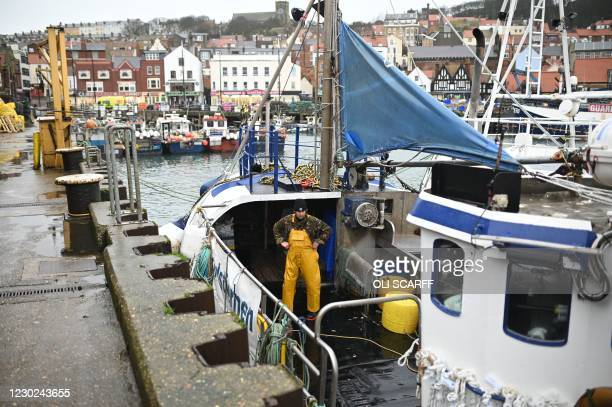 Fisherman washes down his boat in the harbour at Scarborough, northeast England, on December 21, 2020 as the snap closure of the French border over...