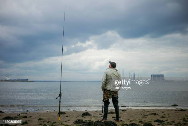 A fisherman watches the tip of his rod for signs of a bite on Bran Sands beach at South Gare on May 19 2019 in Redcar England South Gare is a man...