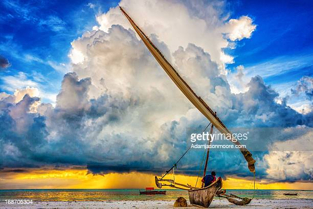 fisherman watching storm cloud, zanzibar - zanzibar stock photos and pictures