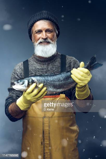 fisherman with a big fish on stormy background - fisherman stock pictures, royalty-free photos & images