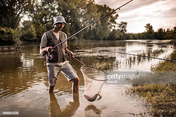 fisherman with a fish in net going out of water. - carp stock photos and pictures