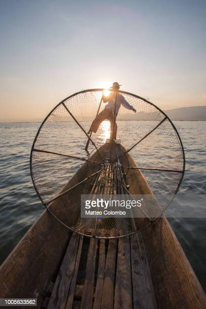 Fisherman with basket fishing from boat, Inle lake, Myanmar (Burma)