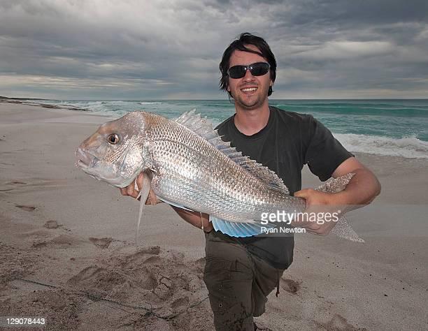 fisherman with big snapper from beach - alleen één mid volwassen man stockfoto's en -beelden
