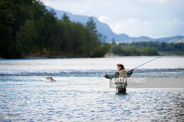 Fisherman with fish jumping