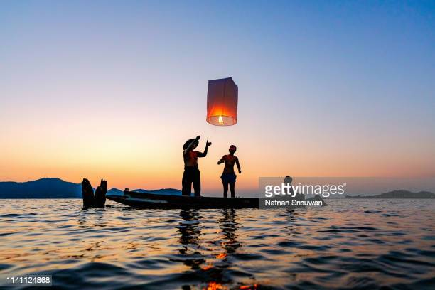 fisherman with floating lamp. - lantern stock pictures, royalty-free photos & images