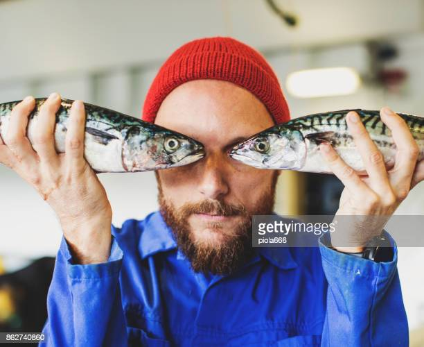 Pescador con pescado fresco en la cubierta del barco de pesca