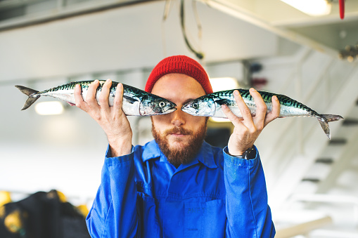 Fisherman with fresh fish on the fishing boat deck 862740864
