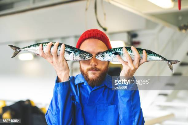 fisherman with fresh fish on the fishing boat deck - bizarre stock pictures, royalty-free photos & images