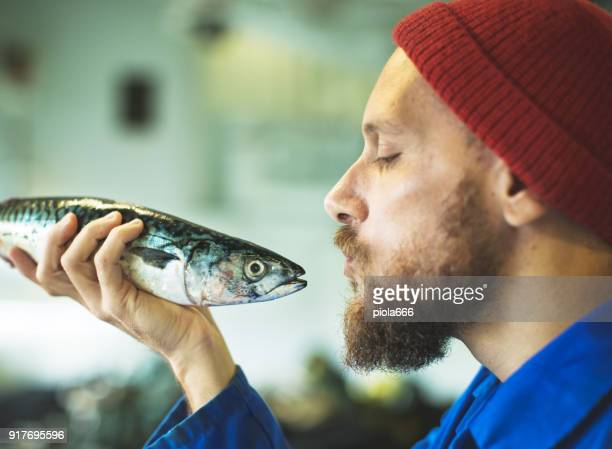 Fisherman with fresh fish on the fishing boat deck