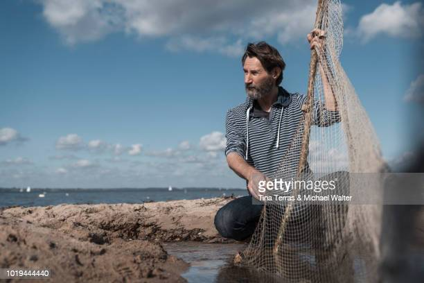 a fisherman with his net at work on the beach - schleswig holstein stock photos and pictures