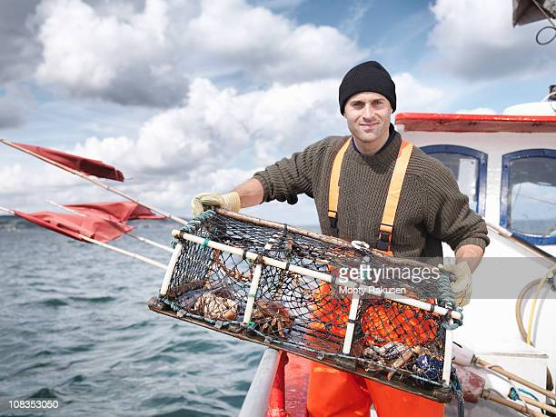 Fisherman with lobster pot and crabs
