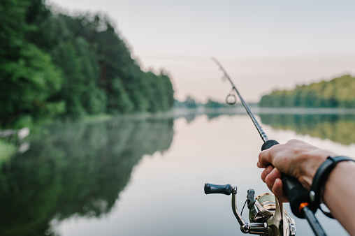 Fisherman with rod, spinning reel on the river bank. Sunrise. Fishing for pike, perch, carp. Fog against the backdrop of lake. background Misty morning. wild nature. The concept of a rural getaway. 1092160614