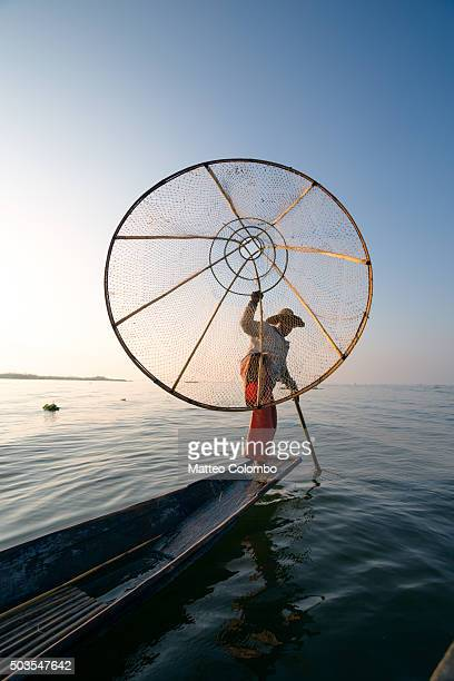 fisherman with typical large basket fishing from his boat, inle lake - myanmar culture stock pictures, royalty-free photos & images