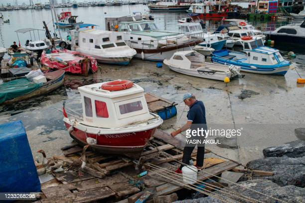 Fisherman works near a boat on the Marmara sea, covered with mucilage in Istanbul, on June 4, 2021. - The mucilage, also reffered to as sea snot, is...