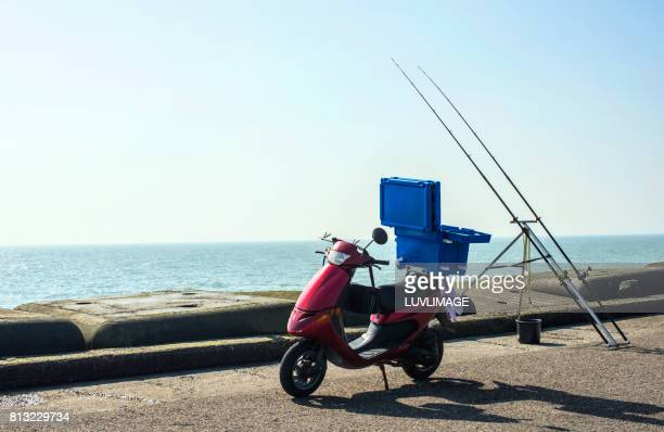 Fisherman's scooter on the pier with fishing rods.