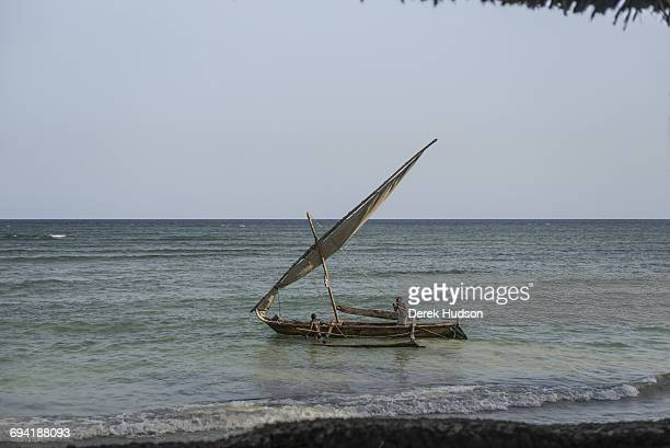 Fisherman's simple dugout boat with outriggers sails past a tourist resort bungalow nearby the beach at Msambweni.The small fishing town and...