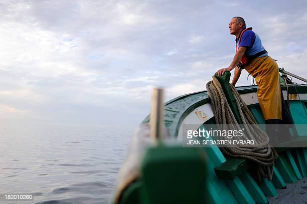 A fishermen aboard the fishing boat 'Kanedevenn' observes the horizon as he sails in search of sardines on September 24 2013 in Quiberon western...