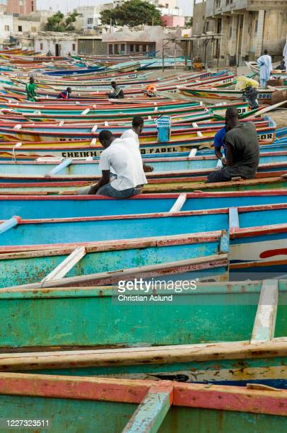 fishermen and pirogue boats on the beach in the picturesque harbour of n'gor, ngor, outside dakar in senegal. - dakar photos et images de collection
