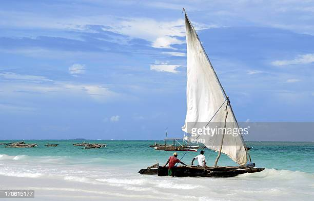 fishermen and their dhow, kiwengwa beach,zanzibar,tanzania - zanzibar island stock photos and pictures
