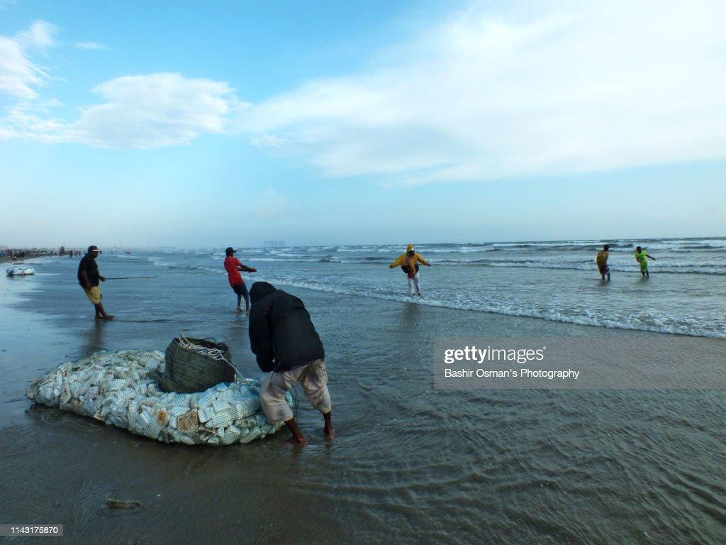 Fishermen Are Busy Doing Fishing By Clifton Beach Of Karachi