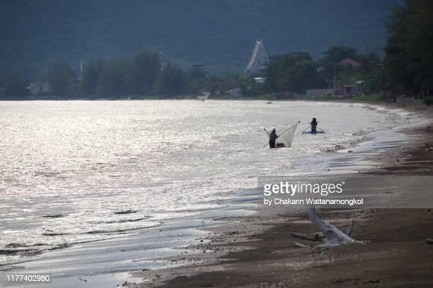 fishermen are working near the beach at sunset with mountain and buddhist temple in the background. - chanthaburi sea stock pictures, royalty-free photos & images