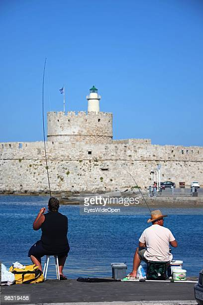 Fishermen at Mandraki Harbour on July 16 2009 in Rhodes Greece Rhodes is the largest of the Greek Dodecanes Islands