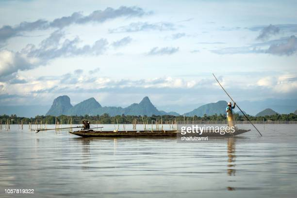 Fishermen at work in long boats, Thailand near Phatthalung province at lake Thale Noi.