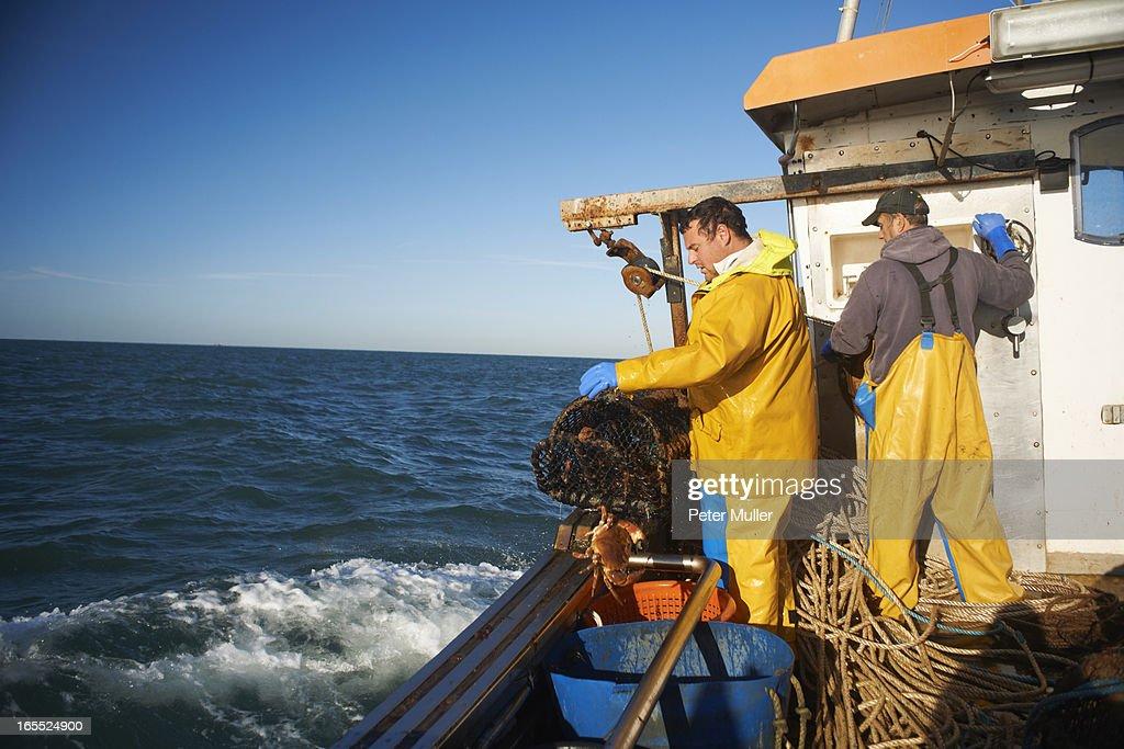 Fishermen at work on boat : Stock Photo