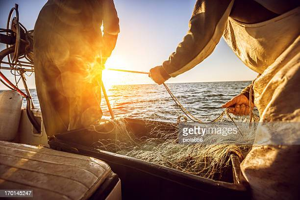 fishermen at work, pulling the nets - fishing industry stock pictures, royalty-free photos & images