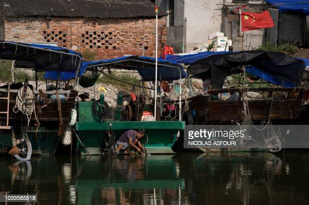 A fishermen attach parts of his boat with a rope ahead of the arrival of the Super Typhoon Mangkhut in Sanhe village on the outskirts of Zhanjiang in...