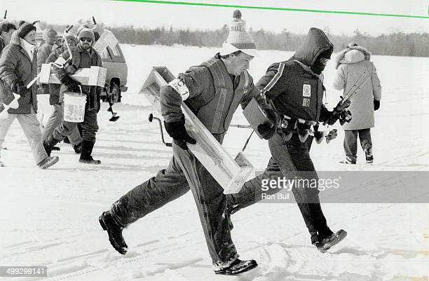 Fishermen Auger for good luck A judge in striped vest sprints with canada's Dave Morton above to his choice of lucky hole in the ice while Finland's...