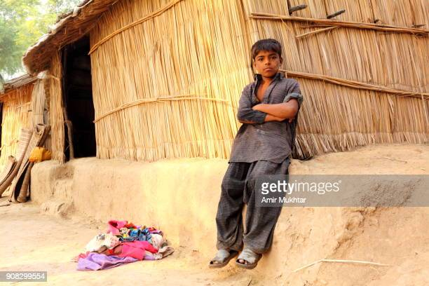 fishermen boy sitting outside his hut - pakistani boys stock photos and pictures