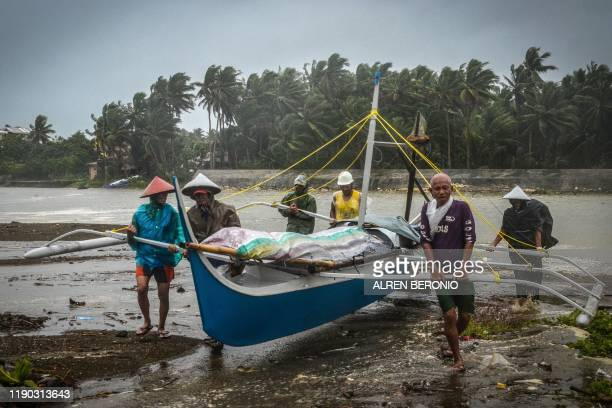 TOPSHOT Fishermen carry a boat to higher ground in Baybay eastern Samar on December 24 after typhoon Phanfone hit the central Philippines Typhoon...