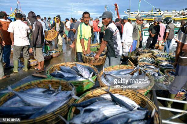 Fishermen carry baskets of fish for sale at the Banda Aceh seaport in Aceh province on November 9 2017 Indonesia's economy grew more slowly than...