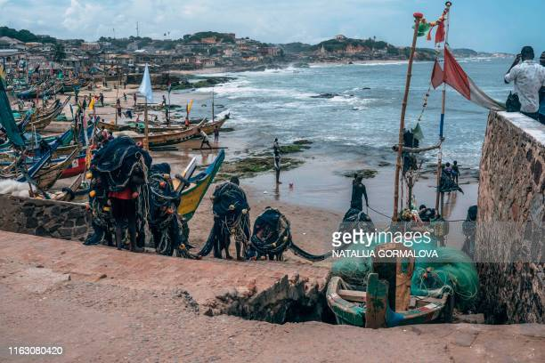 Fishermen carry their nets on August 18 at Cape Coast Castle, as they walk down the same steps many enslaved Africans walked before they were loaded...